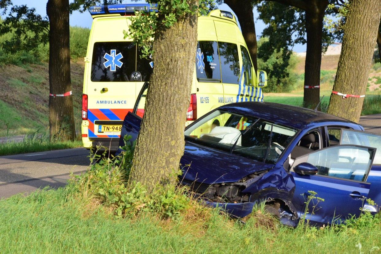 Vrouw raakt met auto van de weg en knalt tegen boom