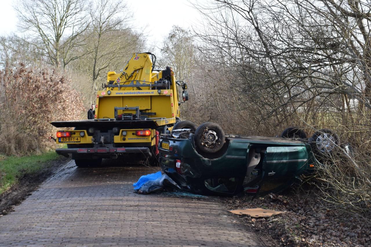 Auto over de kop zwaar beschadigd Drie inzittenden blijven ongedeerd